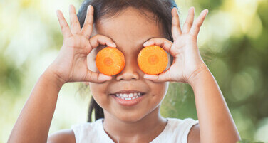 Child holding carrots of her eyes