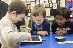 Three kids playing happy on an iPad at school
